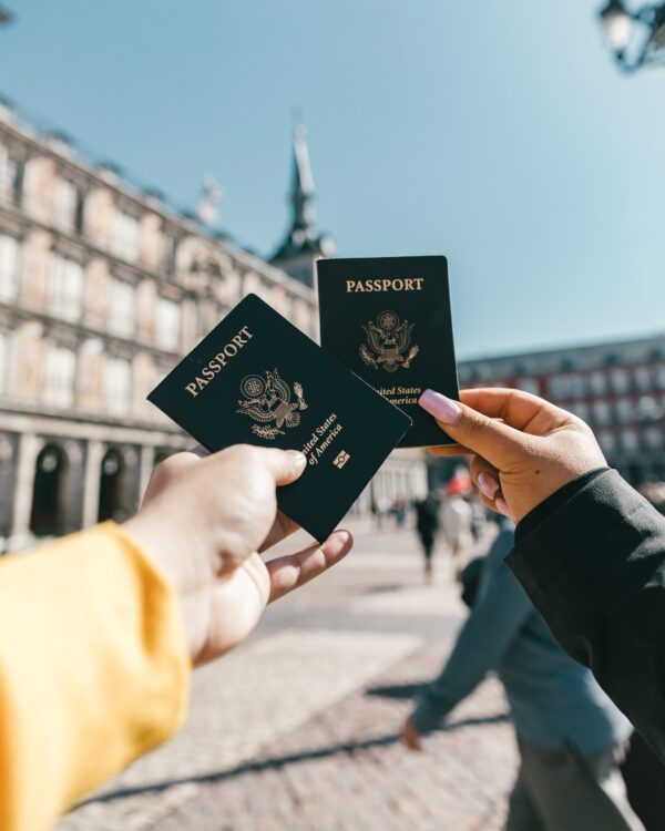 two people holding up passport photos